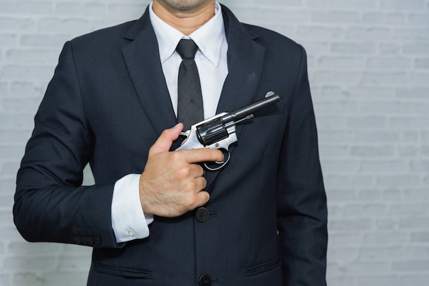 Businessman with gun on gray background Premium Photo