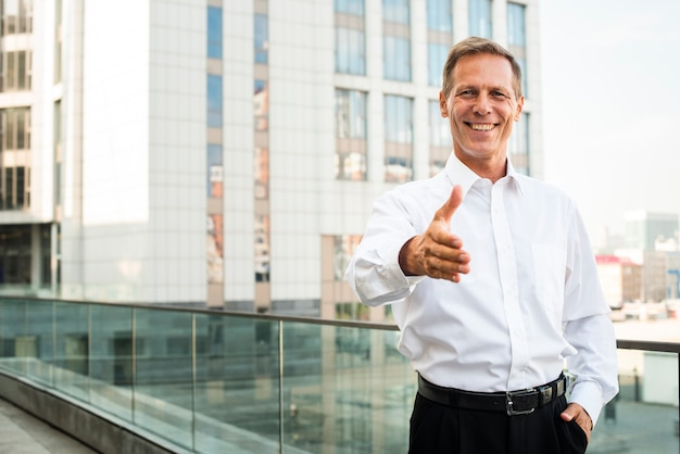 Businessman with hand reaching out Free Photo