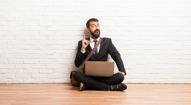 Businessman with his laptop sitting on the floor intending to realizes the solution Premium Photo