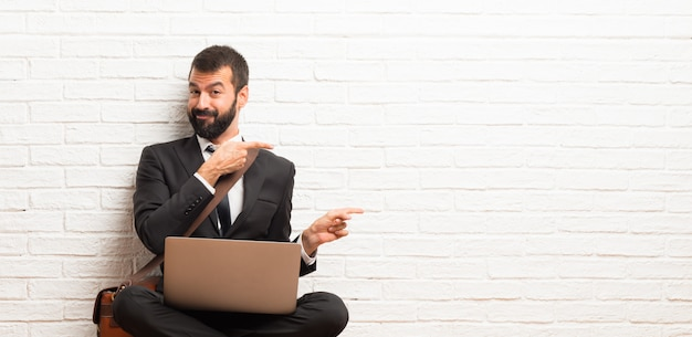 Businessman with his laptop sitting on the floor pointing finger to the side in lateral position Premium Photo