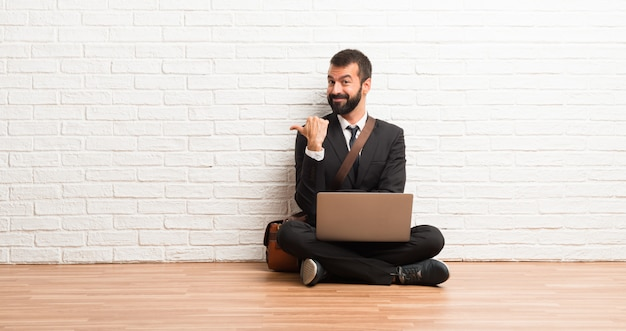 Businessman with his laptop sitting on the floor pointing to the side with a finger to present a product Premium Photo