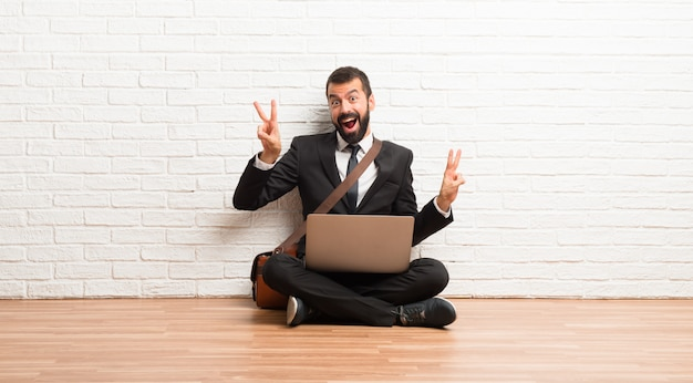 Businessman with his laptop sitting on the floor smiling and showing victory sign with both hands Premium Photo