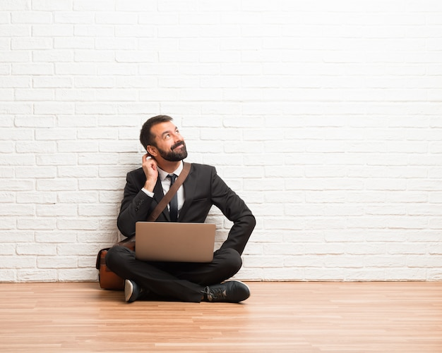Businessman with his laptop sitting on the floor standing and thinking an idea while scratching head Premium Photo