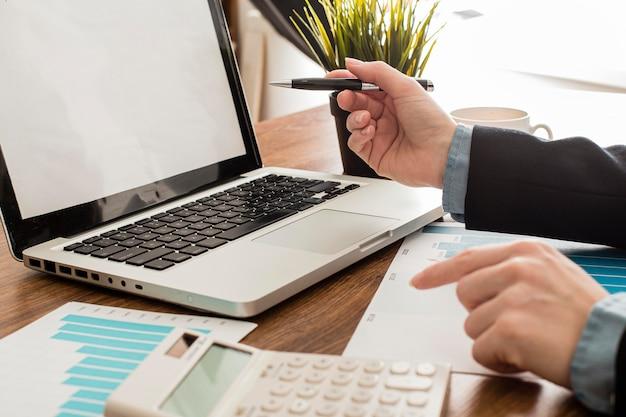 Uomo d'affari con laptop e calcolatrice in ufficio Foto Gratuite
