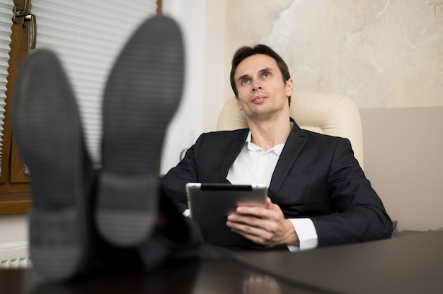 Businessman with legs on desk in office Free Photo