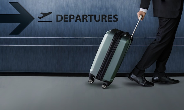 Businessman with luggage walk inside airport departures terminal Premium Photo