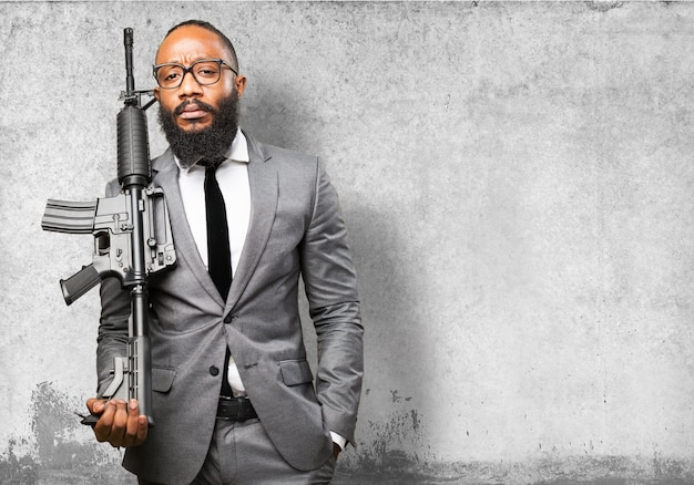 Businessman with machine gun Free Photo