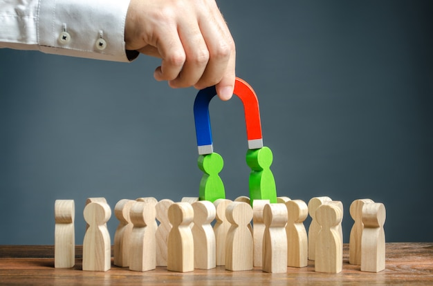Businessman with a magnet pulls green figures of people out of the crowd. recruiting new workers Premium Photo