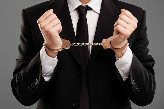 Businessman with manacles on his hands Free Photo