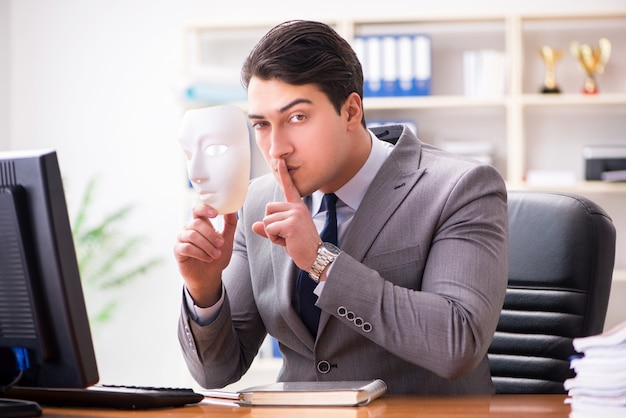 Businessman with mask in office hypocrisy concept Premium Photo