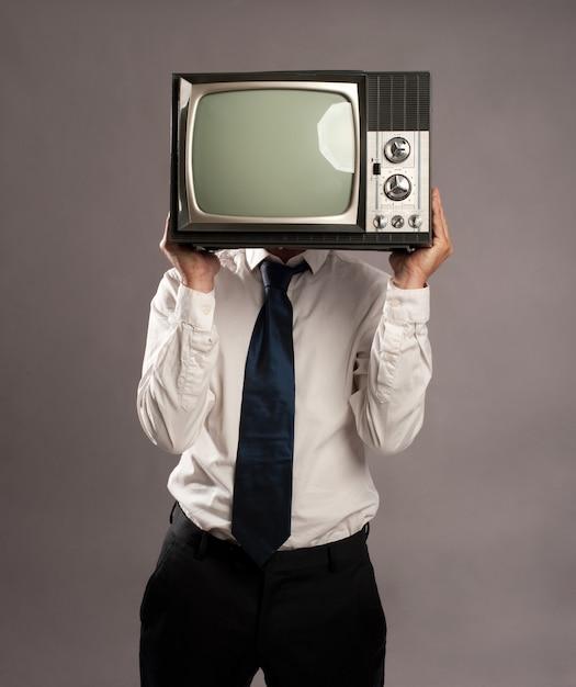 彼の頭に古いレトロなテレビを持つビジネスマン Premium写真