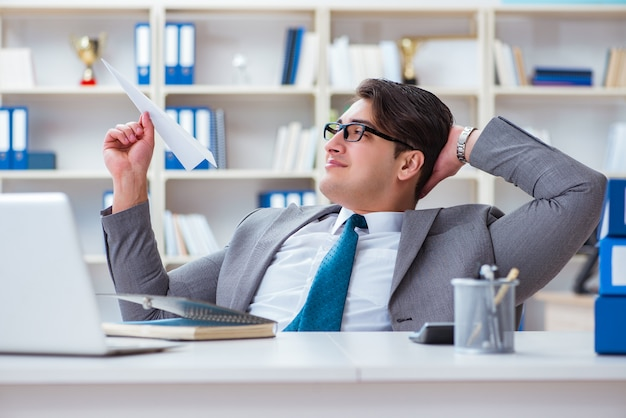 Businessman with paper airplane in office Premium Photo