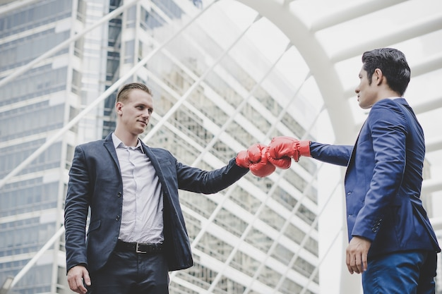 Businessman with red boxing gloves ready to fight his coworker. Free Photo