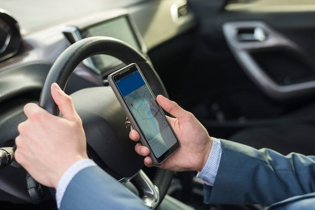 Businessman with smartphone in car Free Photo