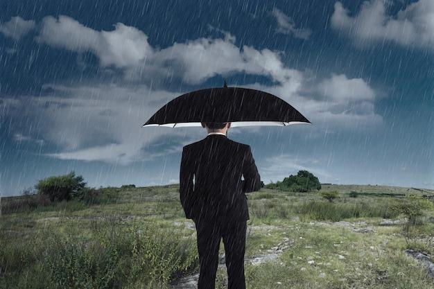Businessman with an umbrella standing under the rain Premium Photo