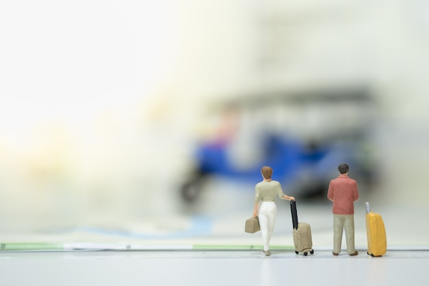 Businessman and woman with baggage standing on map and looking to 3 wheels motor vehicle. Premium Photo