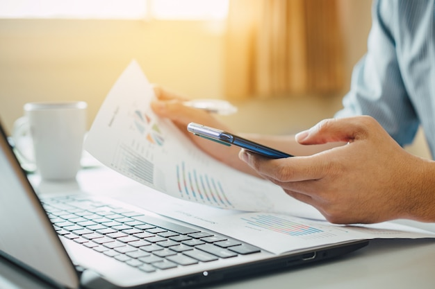 Businessman working at home office with smart phone and laptop computer. Premium Photo