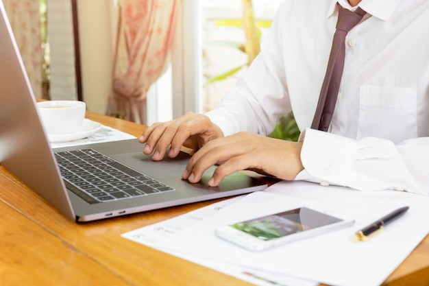 Businessman working on laptop with paperwork on table Premium Photo