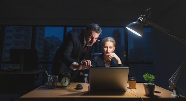 Бизнесмен работает поздно, сидя на столе с секретарем в офисе ночью Premium Фотографии