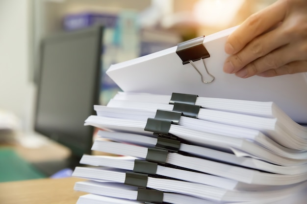 Businessman working in stacks paper for searching information on work desk office. Premium Photo