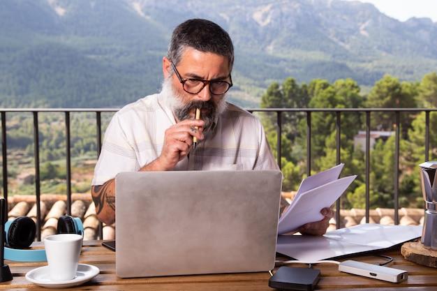 屋外で彼の家のバルコニーでラップトップを使用して作業しているビジネスマン。在宅勤務の概念 Premium写真