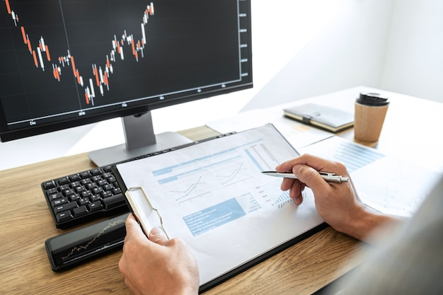 Businessman working with computer and analyzing graph stock market trading with stock chart data Premium Photo