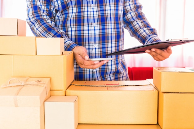 Businessman working with mobile phone and packing brown parcels box at home office. hands seller prepare product ready for deliver to customer. online selling, e-commerce start up shipping concept. Premium Photo