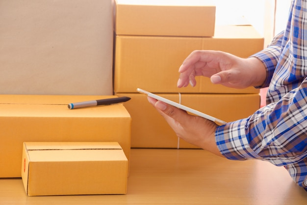 Businessman working with mobile phone and packing brown parcels box at home office Premium Photo