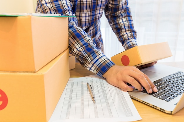 Businessman working with mobile phone and packing brown parcels box at home office. Premium Photo