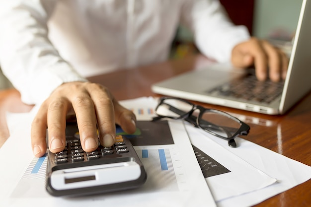 Businessman working with modern workplace with laptop on wood table, man hand on laptop keyboard for work from home, Premium Photo