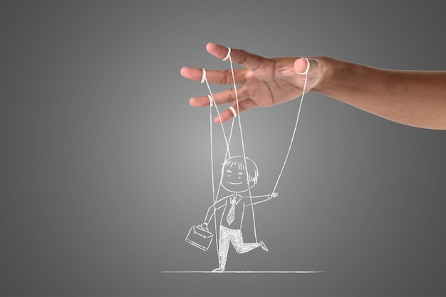 A businessman writes with a white chalk that is controlled by his hand, draw concept. Free Photo