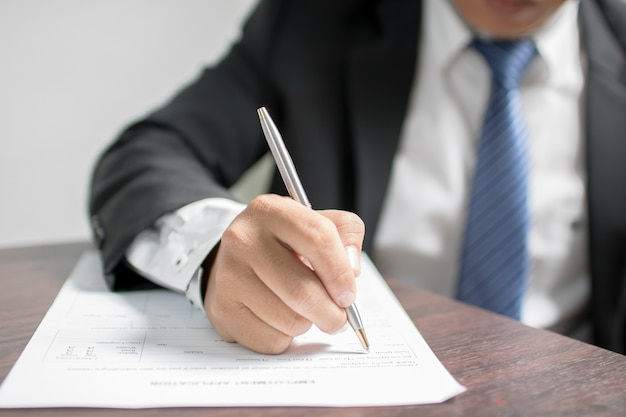 Businessman writing on application form and waiting for interview for get job Premium Photo