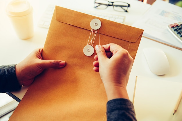 Businessmen are about to open a brown envelope containing business documents Premium Photo