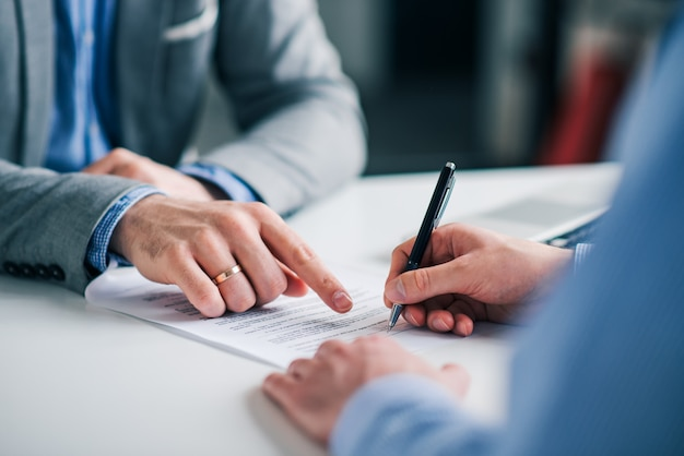 Premium Photo | Businessmen hand's pointing where to sign a contract, legal  papers or application form.