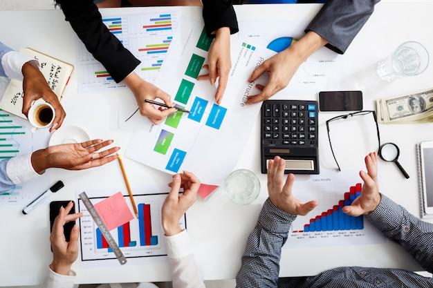 Руки бизнесменов на белом столе с документами и проектами Бесплатные Фотографии