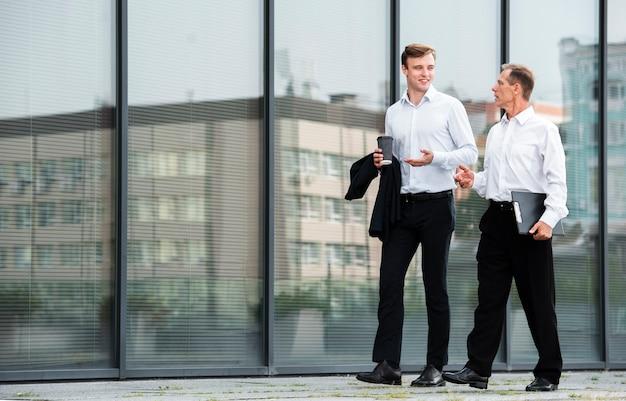 Businessmen having a conversation while walking Free Photo