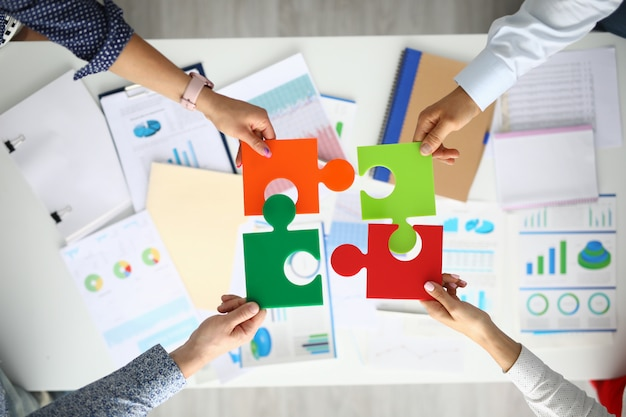 Businessmen hold multicolored puzzles in hand above table with commercial indicators. Premium Photo