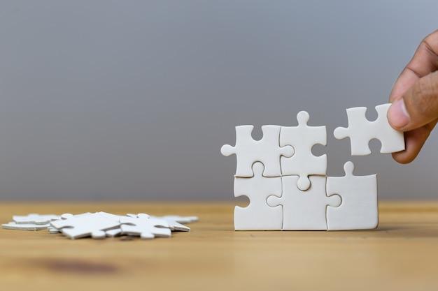 Businessmen put the last puzzle piece, business service concept to success. Premium Photo