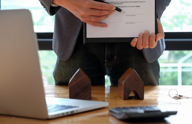 Businessmen selling the house pointing at the signing of the sales contract in the office. Premium Photo
