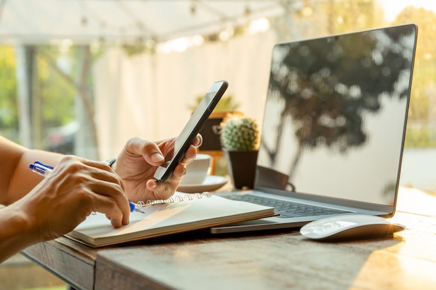 Businessmen using cell phones and writing on notebook with pen on table. Premium Photo