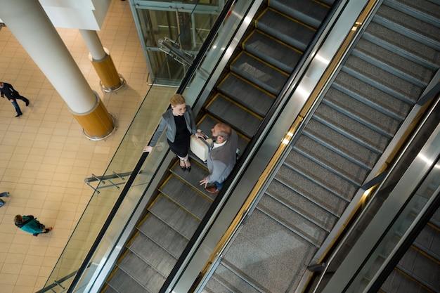 Бизнесмены взаимодействуют друг с другом, спускаясь по эскалатору Бесплатные Фотографии