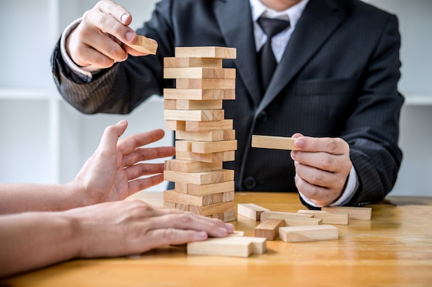 Businesspeople placing and pulling wood block on the tower, alternative risk concept Premium Photo