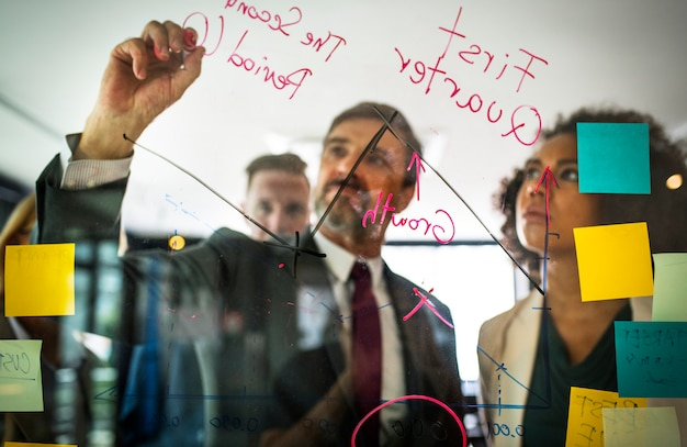 Businesspeople planning on a glass wall Free Photo