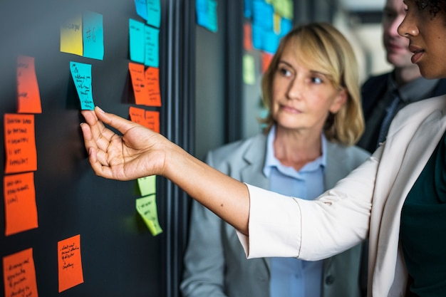 Businesspeople planning tasks with sticky notes Free Photo