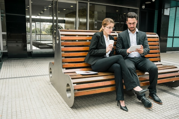 Businesspeople sitting on bench looking at mobile phone Free Photo