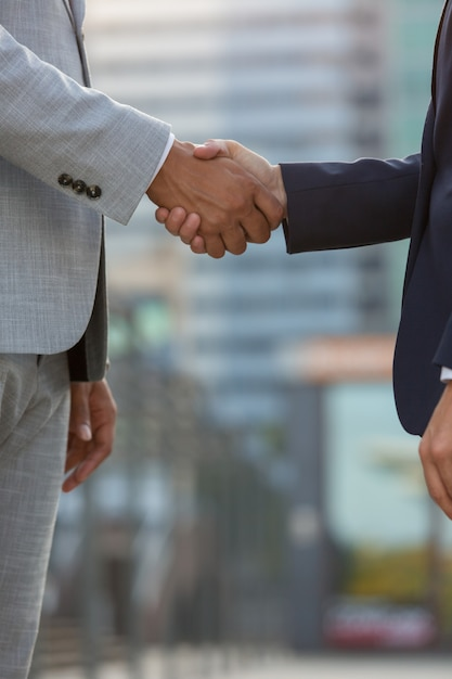 Businesspeople standing in city street and shaking hands Free Photo