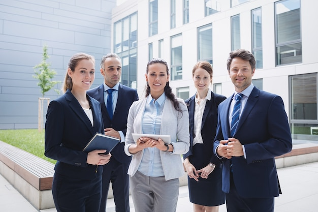 Businesspeople standing outside office building Free Photo