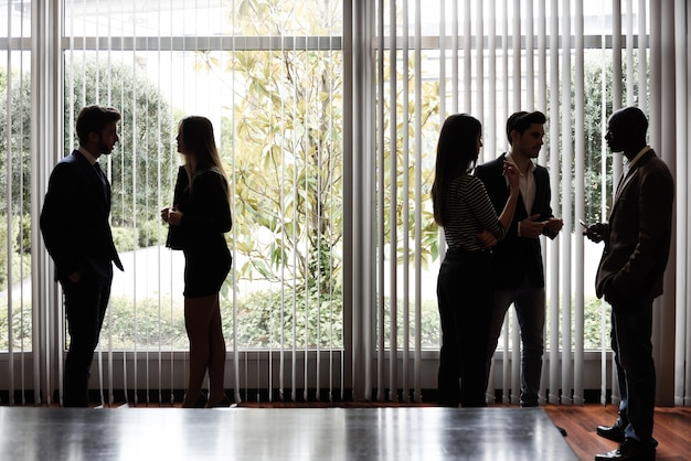 Businesspeople talking close to the window at the office Free Photo
