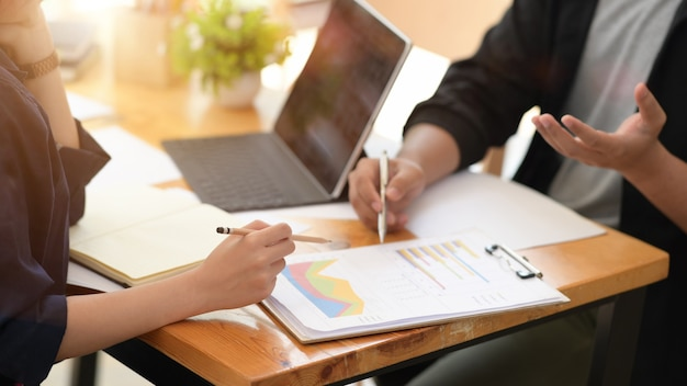 Businesspeople using digital tablet and paper work in office together Premium Photo