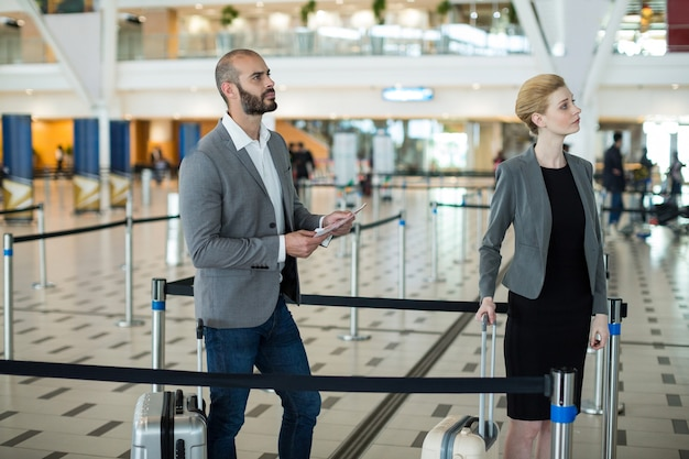 Businesspeople waiting in queue at the check-in counter with luggage Free Photo